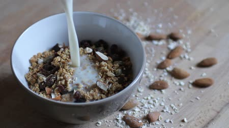 kahvaltı : Pouring oat milk in a bowl with homemade granola Stok Video