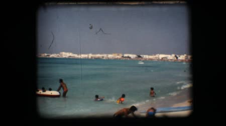 eight : Vintage 8mm. Clear water beach and people playing in the water Stock Footage