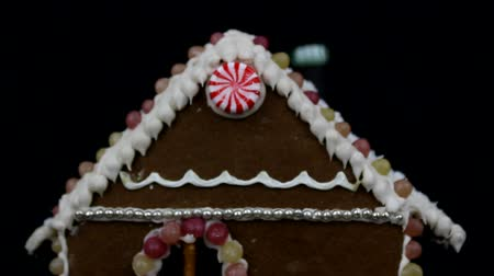 caseiro : Detail of home made gingerbread house with christmas trees on black background Vídeos