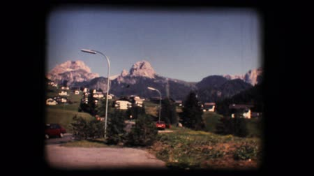 eight : Vintage 8mm. Original footage digitalized. Gardena valley and Dolomite mountains, with cars passing on countryside road Stock Footage