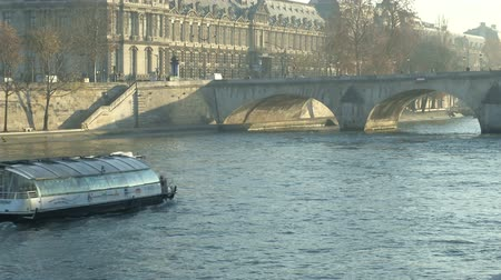 saray : Louvre museum and bridge across the Seine river in Paris, France, with boat passing Stok Video
