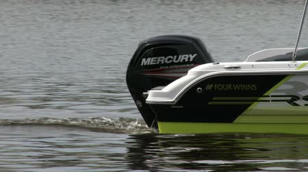 küçük sandal : Small boat navigating slowly on a river, with detail of the outboard engine