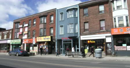 architecture and urbanism : Establishing shot of street with ethnic stores in Korea town neighbourhood in Toronto, Canada