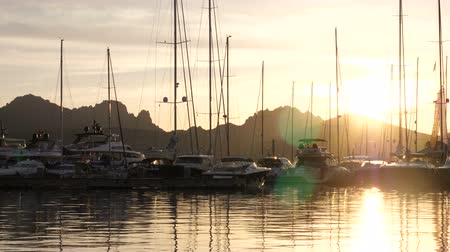 richness : Backlit view of power and sailing boats docked at the sunset in Porto Rotondo, Italy