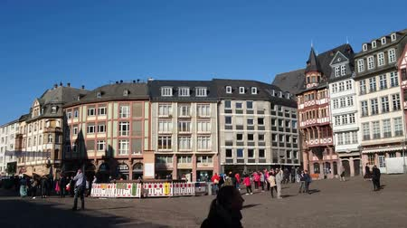 Tourists walk in small square facing old traditional buildings in Frankfurt, Germany.