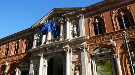 European and Italian flags wave on the main building of the Statale, a public university in Milan, Italy .. Стоковые видеозаписи