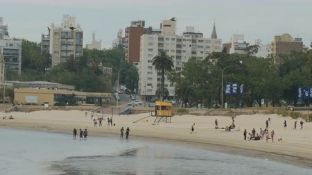 People walk on Playa Ramirez in Montevideo, Uruguay, on December 8, 2017.