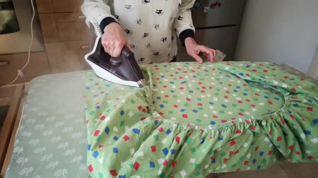 Lady ironing at the Green House Sheet on the Ironing Board: Slow Motion