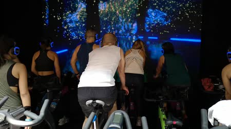 Rimini, Italy - may 2019: Workout with Spinning Bike in front of a technological path on screen at Rimini Wellness 2019.