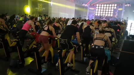 kaslar : Rimini, Italy - may 2019: Workout with Spinning Bike at Rimini Wellness 2019. Stok Video