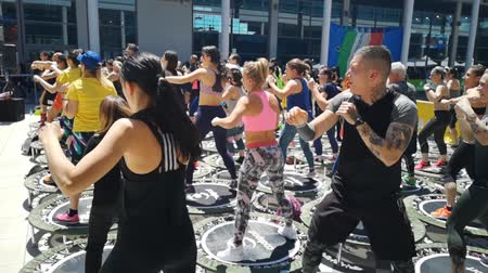 Rimini, Italy - may 2019: Mini Rebounder Workout - People doing Fitness Exercise in Class at Gym with Music and Teacher on Stage