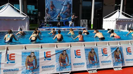 Rimini, Italy - June 2019: People Doing Water Aerobics Outdoor in a Swimming Pool with Bike, Music and Metallic Support Tool
