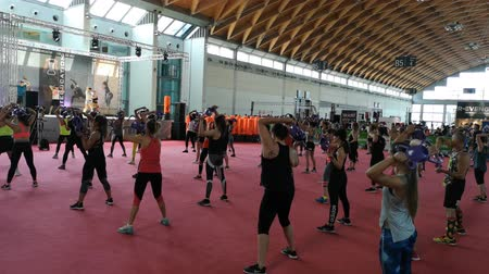 Rimini, Italy - June 2019: Fitness Workout in Gym - People doing Exercises during Public Event with Music and Teacher on Stage