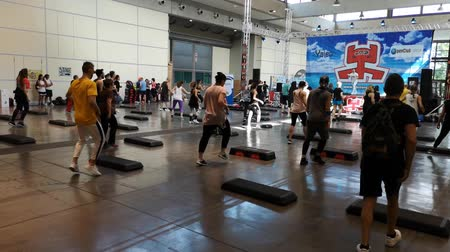 Rimini, Italy - June 2019: Fitness Workout in Gym: People doing Exercises in Class with Step Platform with Music and Teacher on Stage
