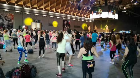 учитель : Rimini, Italy - June 2019: Fitness Workout in Gym - People doing Exercises during Public Event with Music, Dumbells and Teacher on Stage