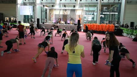 Rimini, Italy - June 2019: Fitness Workout in Gym - People doing Exercises during Public Event with Music, Dumbells and Teacher on Stage