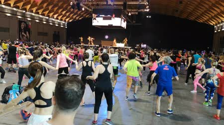 Rimini, Italy - June 2019: Fitness Workout in Gym - People doing Zumba Exercises during Public Event with Music and Teacher on Stage Стоковые видеозаписи