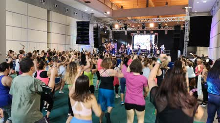 aerobic : Rimini, Italy - June 2019: Fitness Workout in Gym - People doing Exercises during Public Event with Music and Teacher on Stage