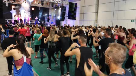 aerobica : Rimini, Italy - June 2019: Fitness Workout in Gym - People doing Exercises during Public Event with Music and Teacher on Stage