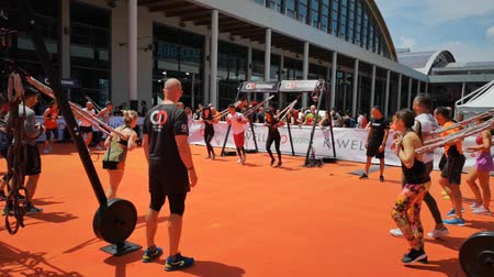 インストラクター : Rimini, Italy - June 2019: People doing Fitness Workout Outdoor with Elastic Rope, Music and Teacher