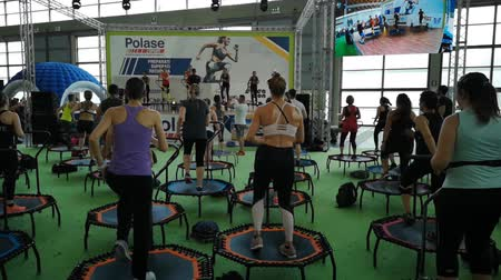 Rimini, Italy - June 2019: Mini Rebounder Workout - People doing Fitness Exercise in Class at Gym with Music and Teacher on Stage