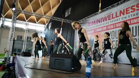 Rimini, Italy - June 2019: Fitness Teachers Give a Demonstration Performance on Stage with Music and Green Drum Stick