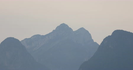 panoramic view of mountain peaks in the Dolomites in northern Italy, just before it comes the night, with a little foggy and rainy mood