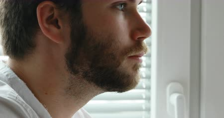 Bearded man working at his laptop and daydreaming watching outside his office window Stock Footage