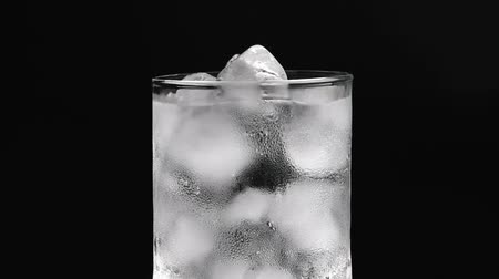 buzlu : Glass cup with ice and water on black background Stok Video