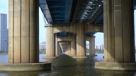The flow of the river under the bridge. Under Dongjak Bridge in Seoul, South Korea. Stok Video