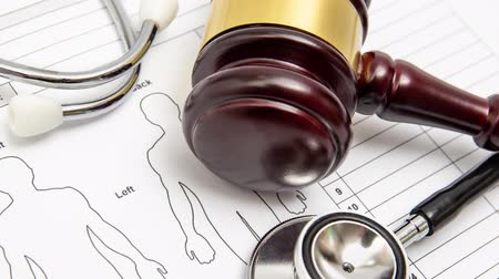 tribunal : Zoom out. A wooden judge gavel and stethoscope on a medical chart. Medical dispute concept. Stock Footage