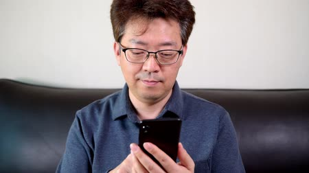 meia idade : Asian middle-aged male trying to read something on his mobile phone.