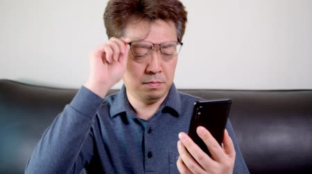 sight seeing : Asian middle-aged male trying to read something on his mobile phone. presbyopia, myopia.