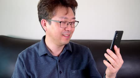 Asian middle-aged man having a happy video call using a smartphone.