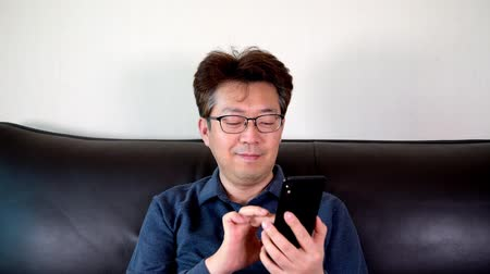 Asian middle-aged male trying to read something on his mobile phone.