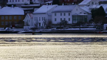 собственность : Man in kayak paddles in front of Norwegian snow covered houses - Some deal with Christmas in their own way