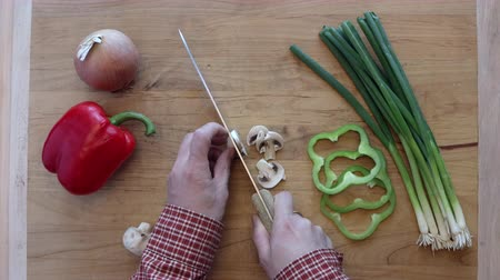 A video clip of cutting mushrooms and other vegetables waiting to be cut on a cutting board. Stok Video