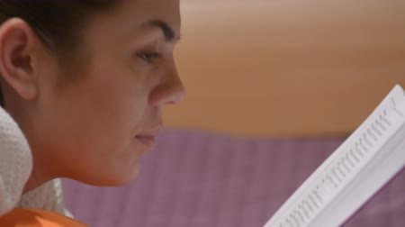 enciclopédia : Girl reading a book lying on the bed Stock Footage
