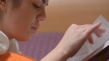 defter : Girl reading a book lying on the bed Stok Video