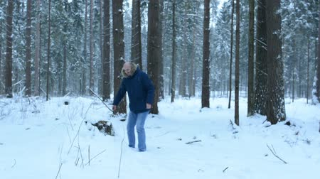 beardie : Man in the woods on a stump, throwing snowballs. Jumping from the stump Stock Footage