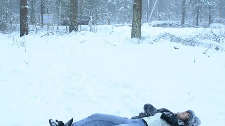 snow angel : Funny playful girl fooling around in the snow and walks in the woods. Snow fall down.