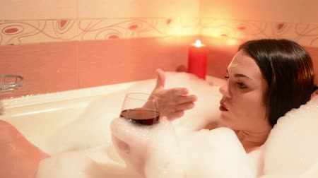 джакузи : Beautiful girl taking a bubble bath with a glass of wine. A large white bath and joy on his face. relaxation concept