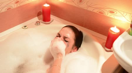 bílé víno : Beautiful young woman relaxing in jacuzzi hot tub spa resort, by romantic candles background. Immersed in the foam, cries and laughs. Dostupné videozáznamy