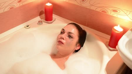 джакузи : Beautiful young woman relaxing in jacuzzi hot tub spa resort, by romantic candles background. Immersed in the foam, cries and laughs. Стоковые видеозаписи