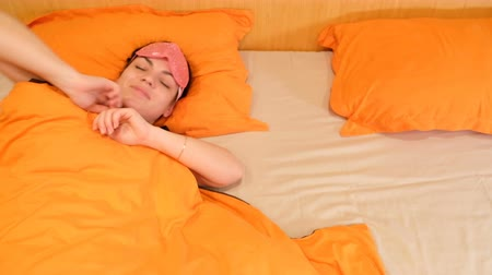probudit se : Closeup of 4k video of a sleeping young woman wearing a blindfold mask. Wakes up and removes the bandage. Aware that he has overslept