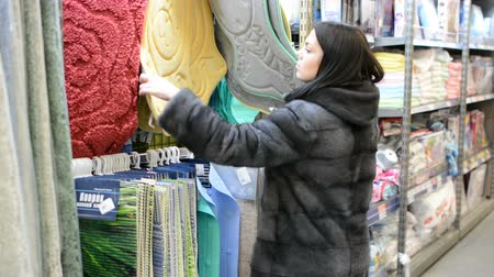 corredor : Beautiful attractive young woman selects rugs on the shelves in the store. Consumerism concept.