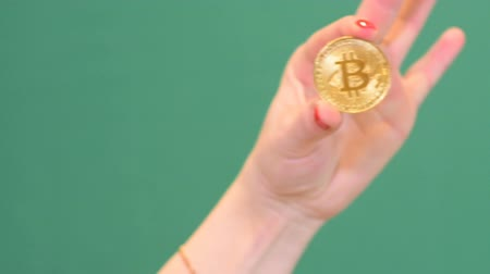 trade show : Hand holds a bitcoin coin, on chroma key background, cryptocurrency, blurred.