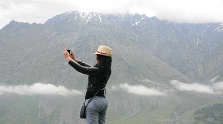 facetime : Young woman uses a smartphone to video a beautiful view in the mountains Stock Footage