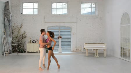 гимнастика : Girl with a guy rehearsing dance in the hall, gymnastic dance in the dance hall
