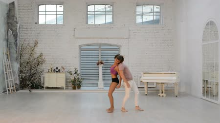 flexionar : Girl with a guy rehearsing dance in the hall, gymnastic dance in the dance hall